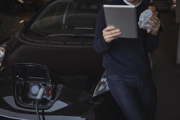 Hombre usando tableta digital mientras carga el coche eléctrico Foto gratis