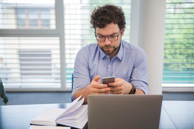 Hombre usando tel fono en la oficina en el escritorio for Telefono de la oficina