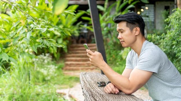 Hombre usando un teléfono inteligente en un balcón Foto Premium