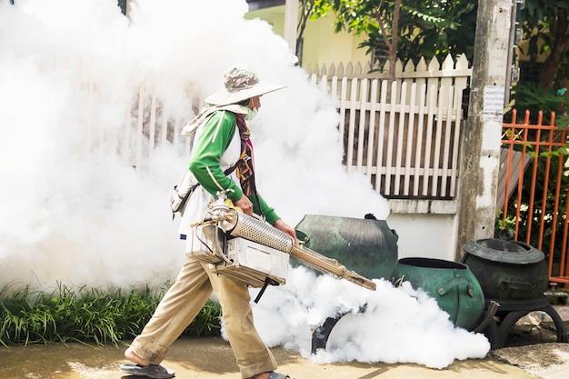 El hombre está utilizando una máquina de niebla térmica para proteger la propagación de mosquitos. Foto gratis