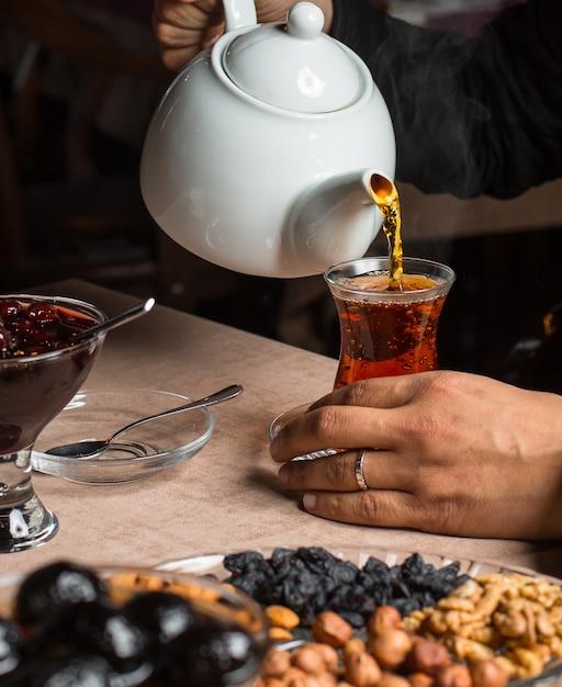 Hombre vertiendo té negro de tetera, servido con frutas secas, mermelada Foto gratis