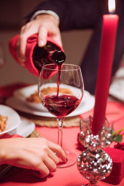 Hombre vertiendo vino en copa en mesa festiva Foto gratis