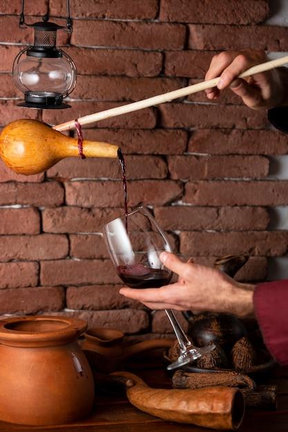 Hombre vertiendo vino tinto de la botella de madera en vidrio Foto gratis