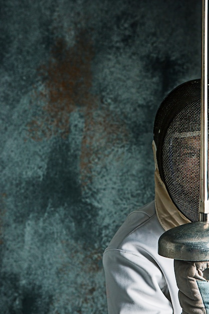 El hombre vestido con traje de esgrima con espada contra gris Foto gratis