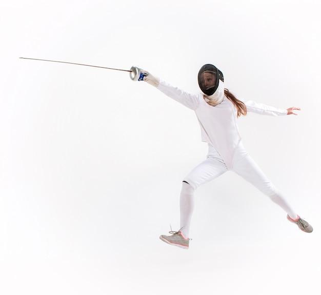 Hombre vestido con traje de esgrima practicando con espada Foto gratis