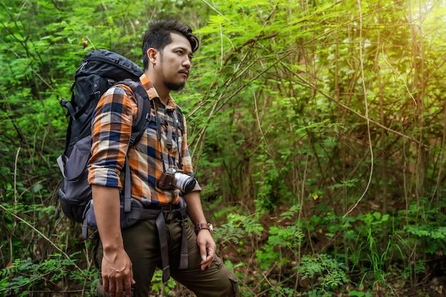 Hombre viajero con mochila en el bosque Foto Premium