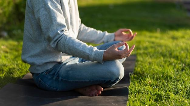 Hombre de vista lateral meditando sobre la hierba Foto gratis