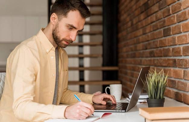 Hombre de vista lateral con videollamada en la computadora portátil y escribiendo Foto Premium
