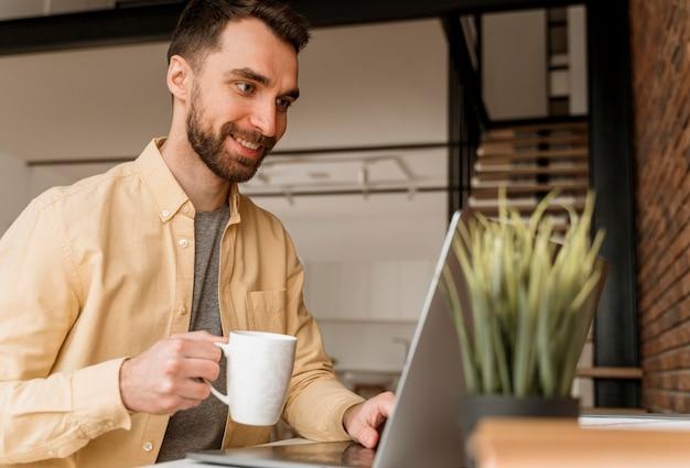 Hombre de vista lateral con videollamada en portátil Foto Premium