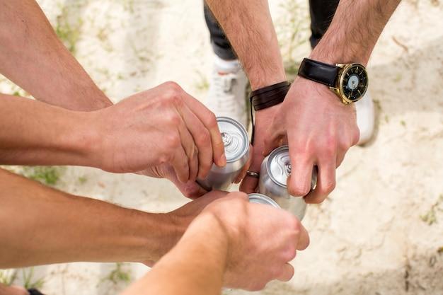 Hombres abriendo latas de cerveza Foto gratis