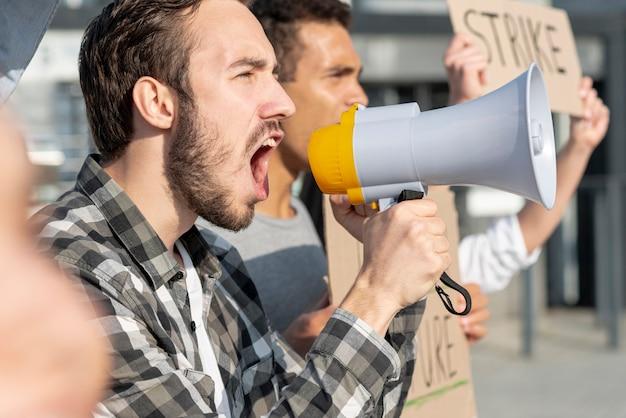 Hombres demostrando junto con megáfono Foto gratis