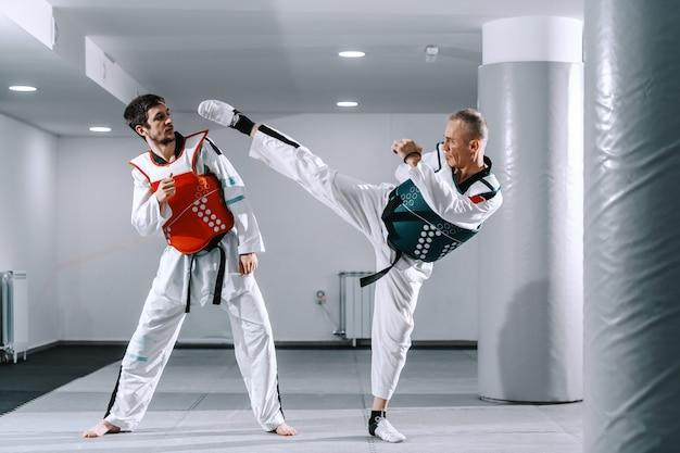 Hombres deportivos entrenando en accesorios de tekwondo. Foto Premium