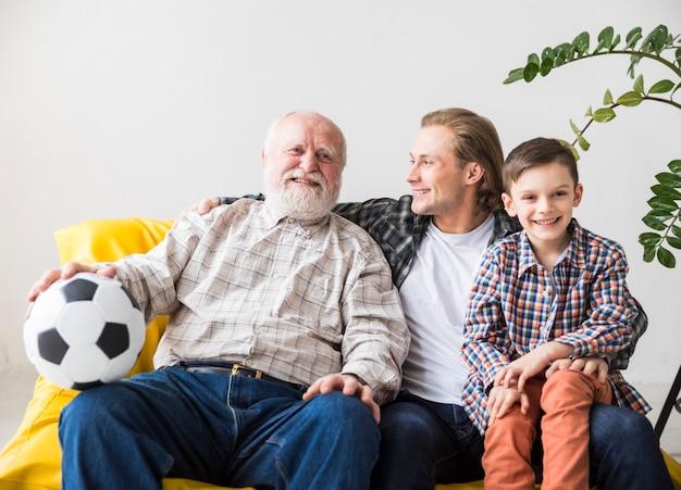 Hombres de diferentes generaciones sentados en el sofá. Foto gratis