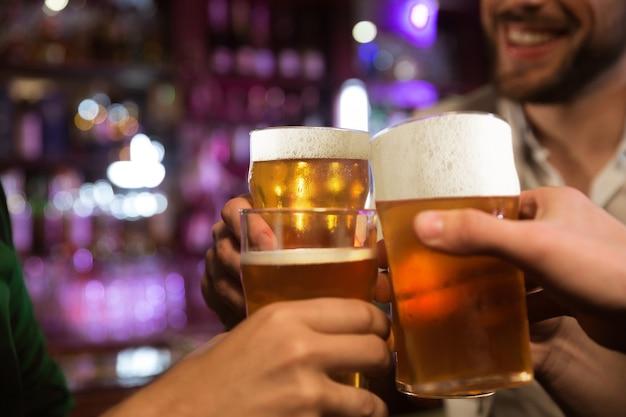 Hombres jóvenes brindando con cerveza mientras están sentados juntos en un pub Foto gratis