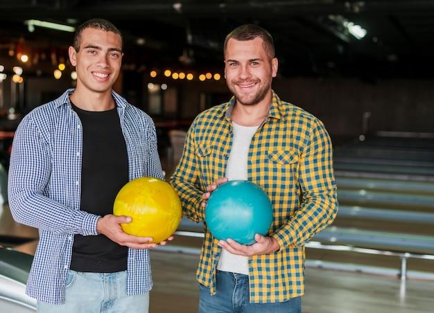 Hombres jovenes que sostienen bolas de bolos coloridas Foto gratis