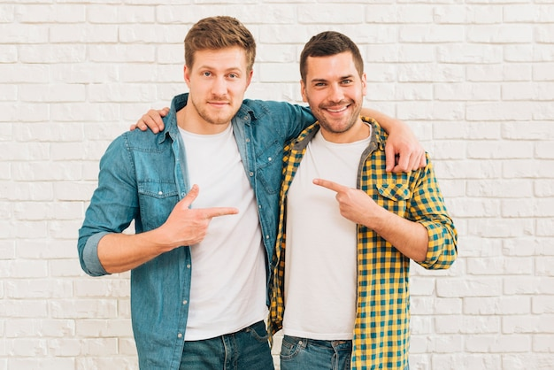 Hombres jóvenes sonrientes con sus brazos alrededor de señalar con los dedos el uno al otro Foto gratis