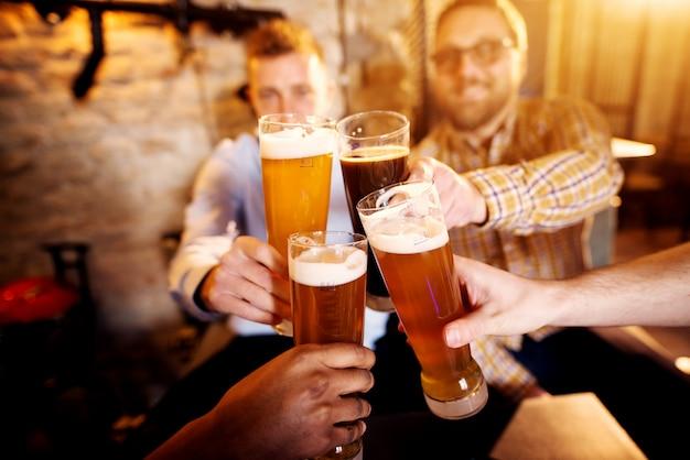 Hombres jóvenes tintineando vasos con una cerveza en el pub soleado. Foto Premium