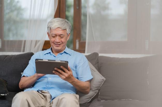 Hombres mayores asiáticos que usan la tableta en casa. información de búsqueda masculino chino mayor asiático sobre cómo buena salud en internet mientras se está acostado en el sofá en concepto de sala de estar en casa. Foto gratis