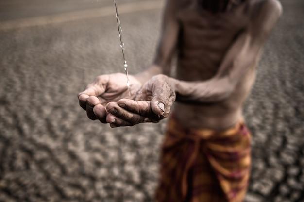 Los hombres mayores están expuestos al agua de lluvia en clima seco, el calentamiento global Foto gratis