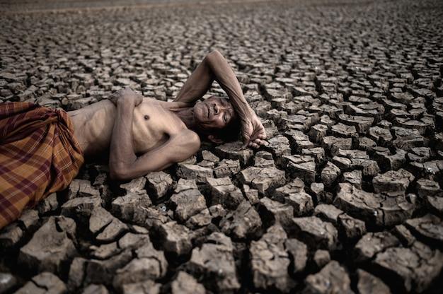 Los hombres mayores yacían acostados sobre sus manos, sobre el estómago y la frente, sobre suelo seco, el calentamiento global. Foto gratis