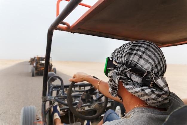 Hombres montando coche buggy en el desierto Foto Premium