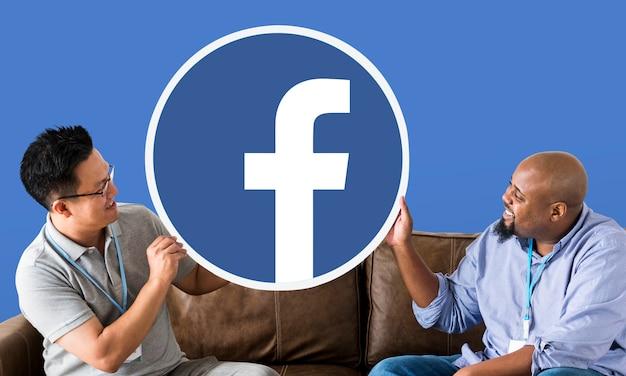 Hombres mostrando un icono de facebook Foto gratis