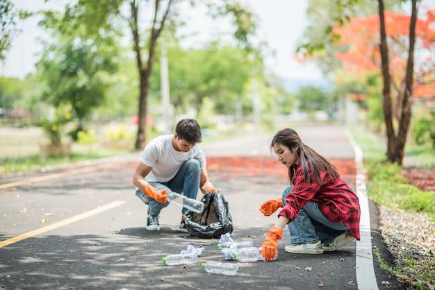 Hombres y mujeres se ayudan mutuamente para recolectar basura. Foto gratis