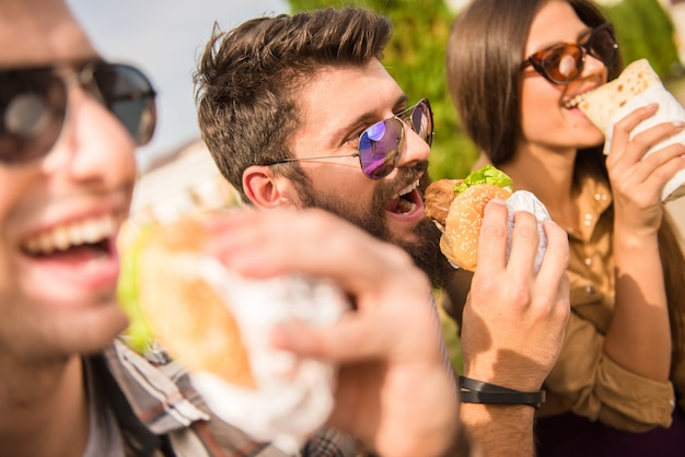 Hombres y mujeres están sentados afuera y comiendo. Foto Premium