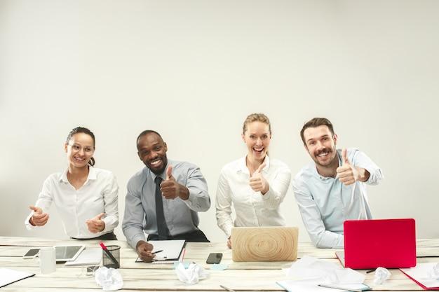 Hombres y mujeres jóvenes sentados en la oficina y trabajando en computadoras portátiles. concepto de emociones Foto gratis