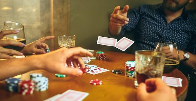 Hombres y mujeres jugando al juego de cartas. poker, entretenimiento nocturno y concepto de emoción. Foto gratis