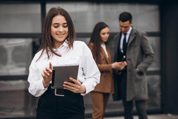 Hombres y mujeres de negocios trabajando en tableta en la oficina Foto gratis