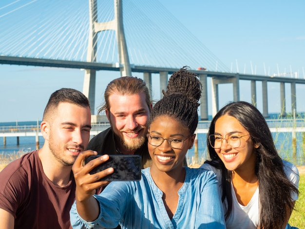 Hombres y mujeres sonrientes que toman selfie al aire libre Foto gratis