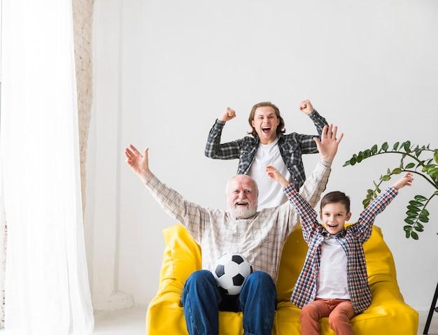 Hombres multigeneración viendo fútbol en televisión regocijándose triunfo Foto gratis