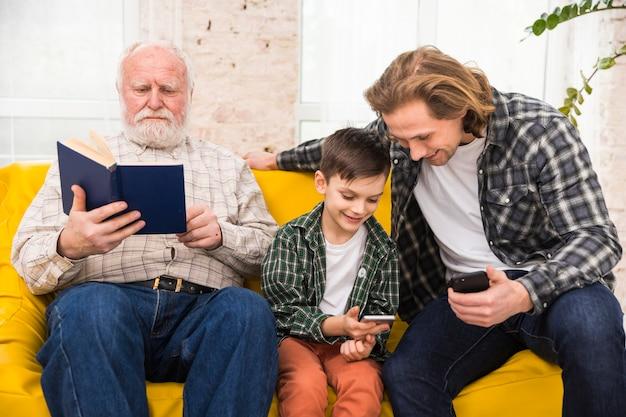 Hombres multigeneracionales que pasan tiempo juntos mirando libros y teléfonos inteligentes. Foto gratis