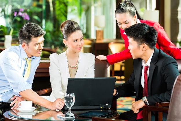 Hombres de negocios asiáticos en la reunión en el vestíbulo del hotel Foto Premium