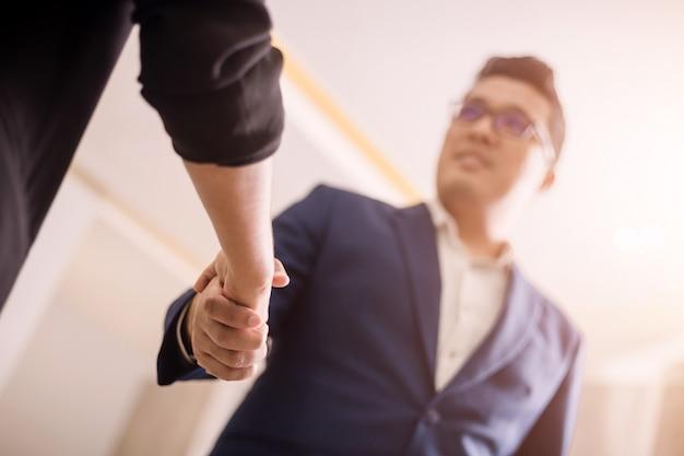 Hombres de negocios dándose la mano, entre la reunión en la sala de seminario Foto Premium
