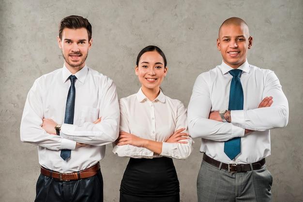 Los hombres de negocios y la empresaria jovenes confiados con sus brazos cruzaron la mirada a la cámara Foto gratis