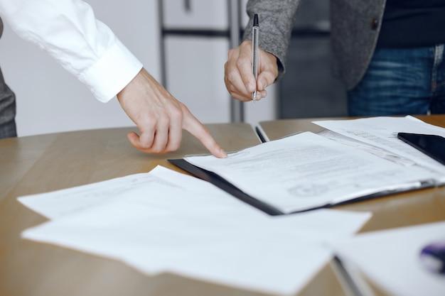 Hombres de negocios sentados en el escritorio de los abogados. personas que firman documentos importantes. Foto gratis