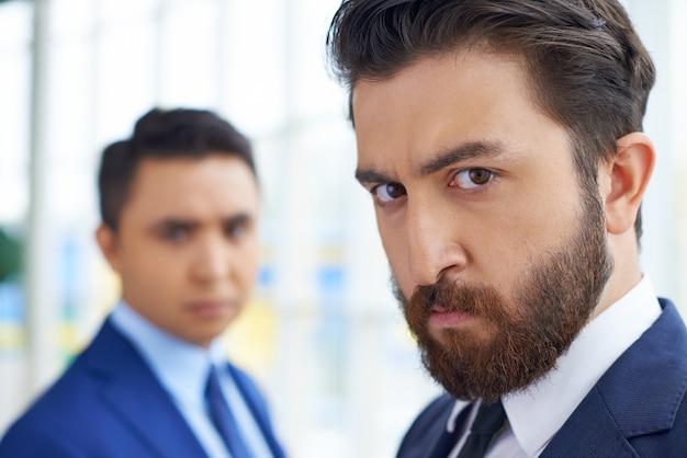 Hombres de negocios serios en la oficina Foto gratis
