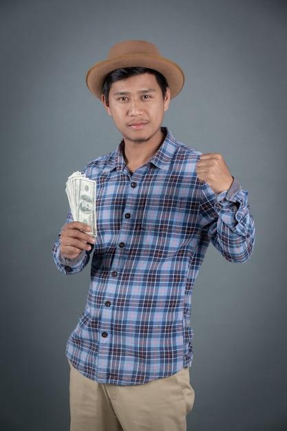 Hombres que sostienen un banco del dólar en un fondo gris. Foto gratis