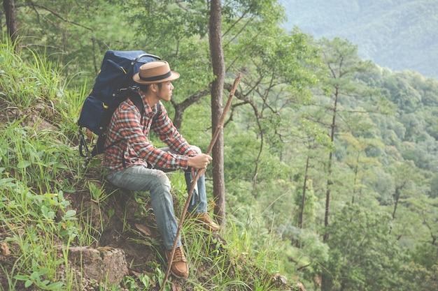 Los hombres se sientan y miran montañas en los bosques tropicales con mochilas en el bosque. aventura, viajar, escalar. Foto gratis