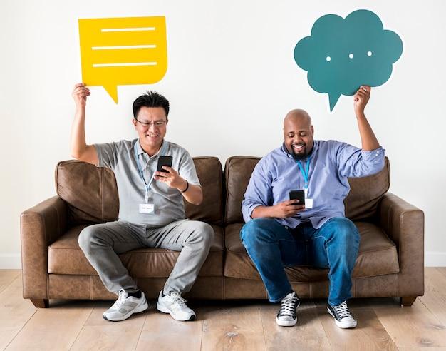 Hombres sosteniendo cajas de mensajes y trabajando en el móvil. Foto Premium