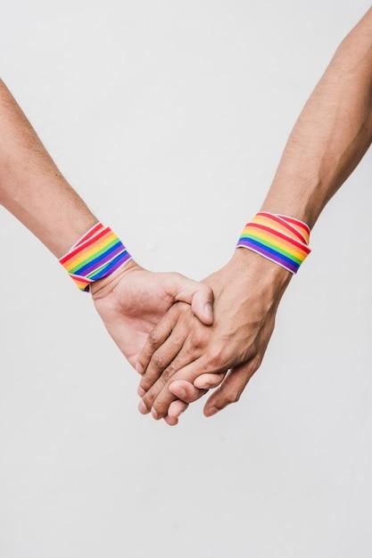 Hombres tomados de las manos con cintas en colores lgbt. Foto gratis
