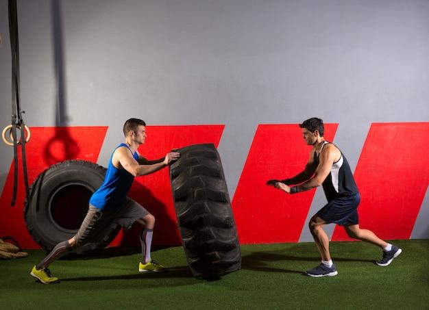 Hombres volteando un neumático de tractor ejercicio de gimnasio ejercicio Foto Premium