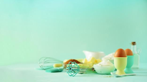 Hora de hornear. ingredientes para hornear: mantequilla, azúcar, harina, huevos, aceite, cuchara, rodillo, cepillo, batidor, leche Foto Premium