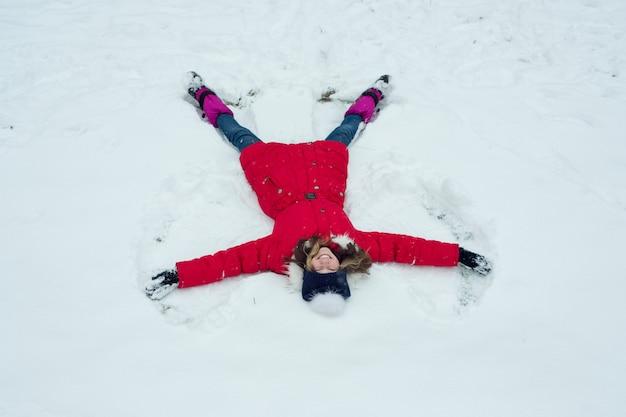 Horario de invierno, alegre niña divirtiéndose en la nieve, vista superior Foto Premium