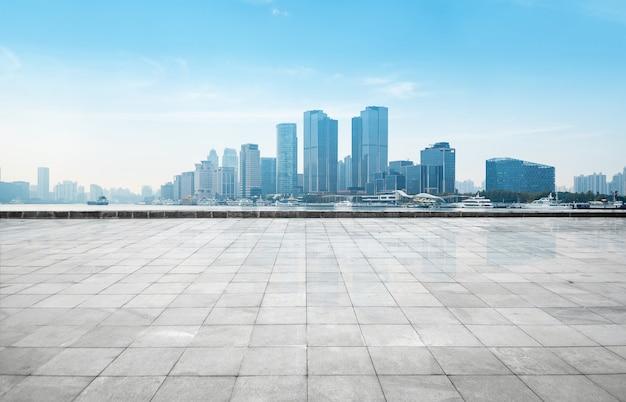 Horizonte panorámico y edificios con piso cuadrado de hormigón vacío, shangai, china Foto Premium