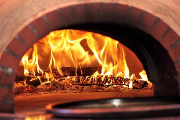Horno de pizza con fuego en restaurante Foto gratis
