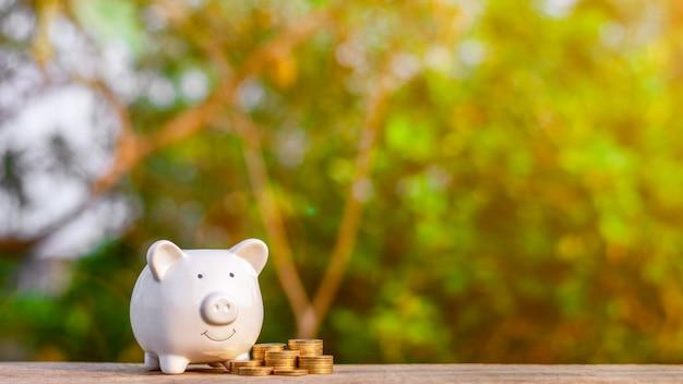 Hucha y una pila de monedas de oro en la mesa de madera vieja. - concepto de negocio y gestión. copyspace Foto Premium