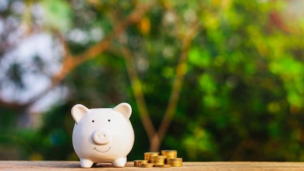 Hucha y una pila de monedas de oro en la mesa de madera vieja. Foto Premium